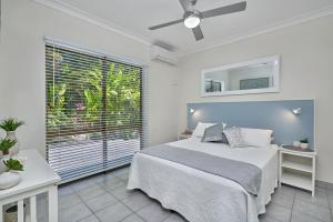 A bed or beds in a room at Cairns Northern Beaches Holiday Retreat