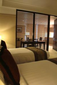 A bed or beds in a room at Pacific Regency Hotel Suites