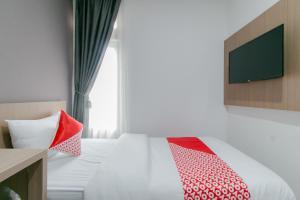 A bed or beds in a room at OYO 2228 Arwinda Costel Syariah