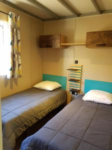 A bed or beds in a room at Camping Calme et Nature