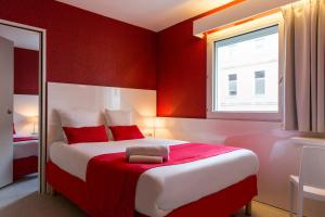 A bed or beds in a room at Hôtel Central Parc Oyonnax