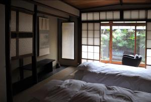 A bed or beds in a room at Traditional Kyoto Inn serving Kyoto cuisine IZYASU - Former Ryokan Izuyasui