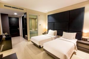 A bed or beds in a room at Grandia Hotel