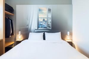 A bed or beds in a room at B&B Hôtel MAUREPAS