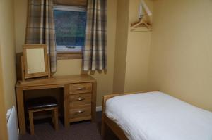 A bed or beds in a room at Myrtle Bank Hotel