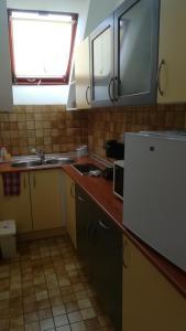 A kitchen or kitchenette at MA-JA apartman