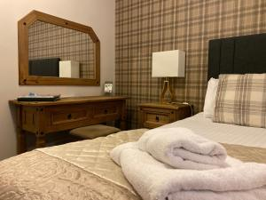 A bed or beds in a room at The Oaks Hotel