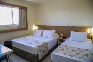 A bed or beds in a room at Hotel Caiuá Express