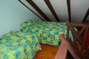 A bed or beds in a room at Gina's Garden Lodges
