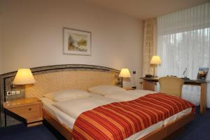 A bed or beds in a room at Hotel Müggelsee Berlin