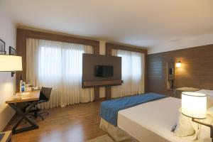 A bed or beds in a room at TRYP By Wyndham Ribeirão Preto