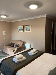 A bed or beds in a room at The Chichester Hotel