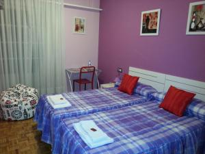 A bed or beds in a room at Pensión Pamplonabeds