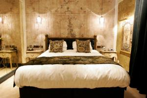 A bed or beds in a room at Hardwick Hall Hotel