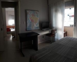 A television and/or entertainment centre at AMPLO 2Dorm. c/Box coberto e segurança 24hs no Menino Deus
