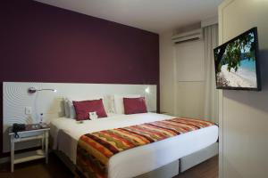 A bed or beds in a room at Quality Suites Alphaville