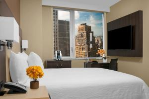 A bed or beds in a room at Hilton Garden Inn Times Square Central