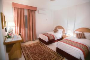 A bed or beds in a room at Petra Plaza Hotel