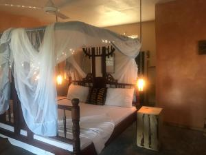 A bed or beds in a room at Mbuyuni Beach Village