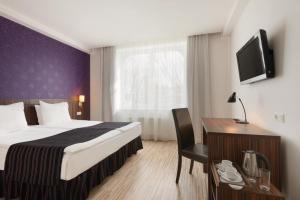 Una televisión o centro de entretenimiento en Rija VEF Hotel with FREE Parking
