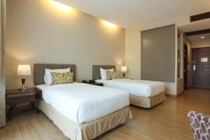 A bed or beds in a room at Le Patta Hotel Chiang Rai