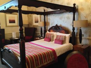 A bed or beds in a room at Coulsdon Manor Hotel and Golf Club