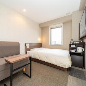 A bed or beds in a room at Super Hotel Joetsu Myoko-Eki Nishiguchi