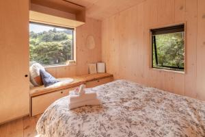 A bed or beds in a room at Bellbird Bach - Akaroa Holiday House