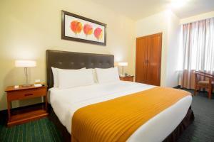 A bed or beds in a room at El Dorado Classic Hotel