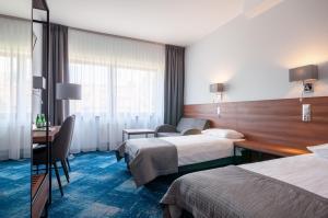 Łóżko lub łóżka w pokoju w obiekcie Hotel Oliwski