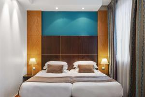 A bed or beds in a room at Best Western Plus Monopole Métropole
