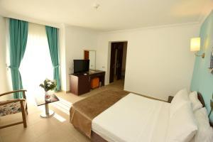 Een bed of bedden in een kamer bij Yelken Mandalinci Spa&Wellness Hotel