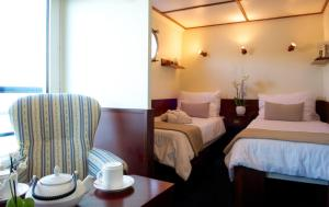 A bed or beds in a room at Bateau Hotel le Chardonnay Avignon