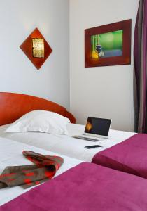 A bed or beds in a room at The Originals City, Hôtel Alteora, Poitiers Site du Futuroscope (Inter-Hotel)
