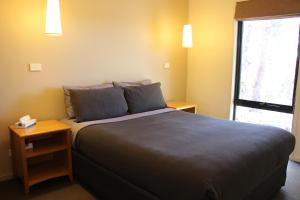 A bed or beds in a room at Cradle Mountain Wilderness Village