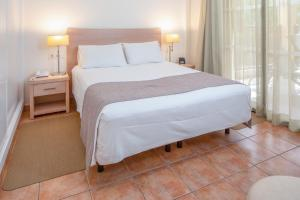 A bed or beds in a room at Royal Sunset Beach Club By Diamond Resorts