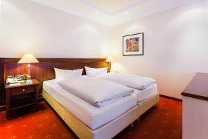 A bed or beds in a room at Hotel Villa Marburg im Park