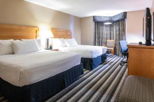 A bed or beds in a room at Royal Hotel West Edmonton, Trademark Collection by Wyndham
