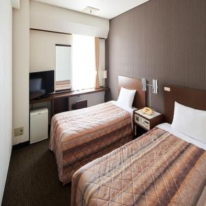 A bed or beds in a room at Marroad Inn Akasaka