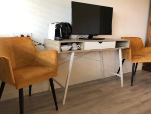 Télévision ou salle de divertissement dans l'établissement Strandhotel Om de Noord