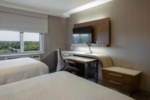 A bed or beds in a room at Courtyard by Marriott New York Queens/Fresh Meadows