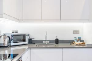 A kitchen or kitchenette at St Albans 2 Bed Luxury City Apartment, 5 mins walk to Train & Allocated Parking