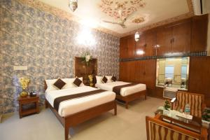 A bed or beds in a room at Virasat Mahal Heritage Hotel