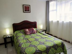A bed or beds in a room at Hotel La Guaria Inn & Suites