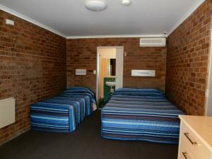 A bed or beds in a room at The Canungra Motel