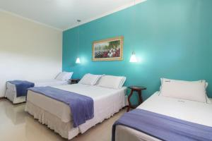 A bed or beds in a room at Pousada Eclipse Paraty