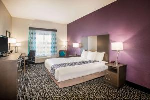 A bed or beds in a room at La Quinta Inn & Suits by Wyndham Pontoon Beach IL