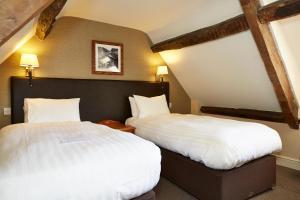 A bed or beds in a room at Woolpack Inn by Greene King Inns