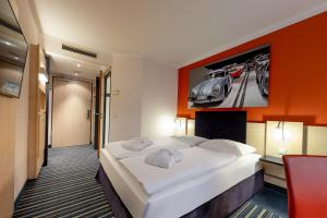 A bed or beds in a room at Mercure Stuttgart City Center