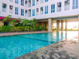 The swimming pool at or near Clean Studio Apartment at Grand Dhika City By Travelio